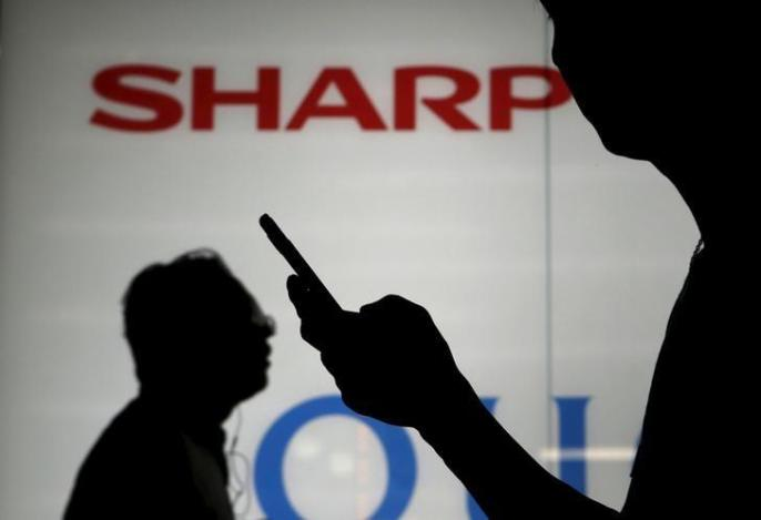 A man using his mobile phone walks past a logo of Sharp Corp outside an electronics shop in Tokyo